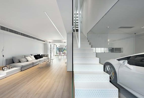 minimalistisches wohnzimmer mit glaswand zur garage, modernem sofa grau, einbaudeckenleuchten, küche mit fensterband, moderne innentreppe aus perforiertem blech