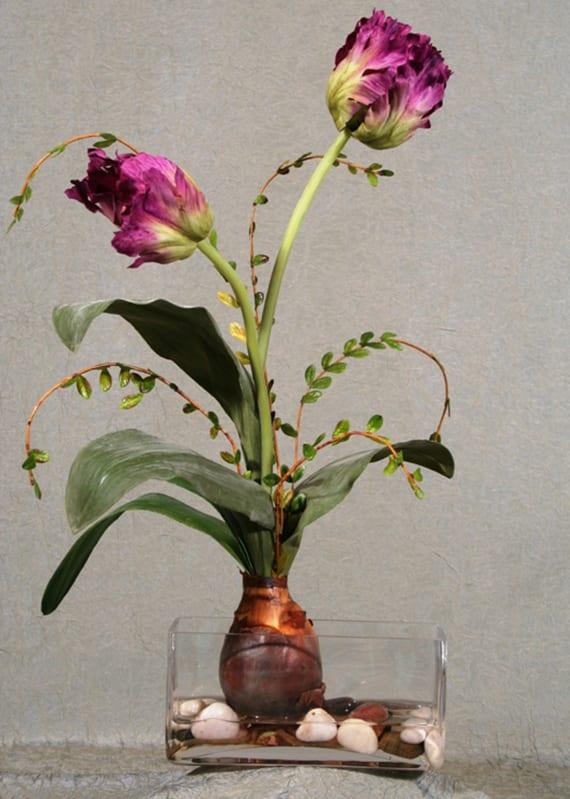 kreative tischdekoration mit lilafarbiger Tulpenzwiebel in rechteckigem Glasgefäß mit Kiselsteinen