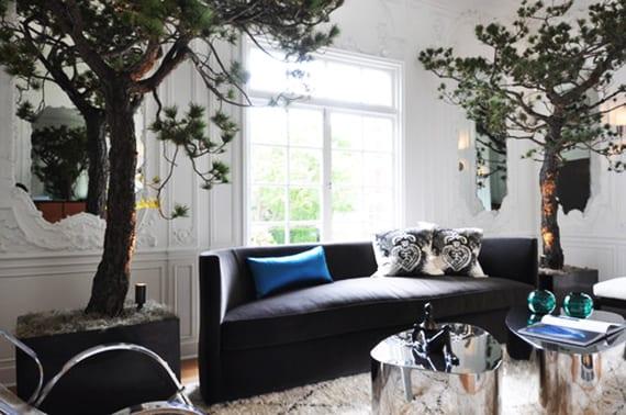 coole wohnzimmergestaltung mit  Monterey-Kiefern in rechteckigen Betonkübeln, gerunderem Sofa grau, Wandgestaltung mit Spiegeln  und klassischen Motiven in weiß, zwei Kaffeetische in Metall-Hochglanz