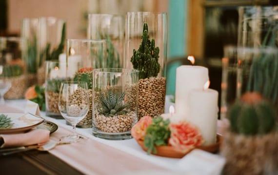 originelle und festliche tischdeko mit weißen kerzen, rosafarbigen böüten, sukkulenten in vasen aus glas und stoffservietten in hellrosa