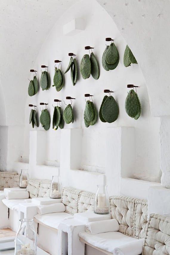 weißes wohnzimmer im metiterranen stil mit ausgemauerten sitzplätzen, diy windlichter mit weißen kerzen,weißen sitzkissen, wandnischen und coole wanddeko in grün mit kaktusblättern