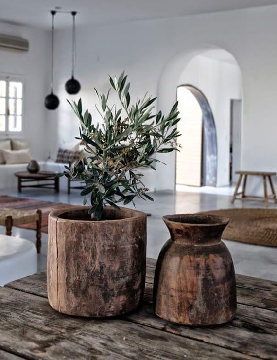 mediterrane raumgestaltung mit ausgemauerter sitzecke,rundem holzcouchtisch,rundem teppich auf zementboden,kugel-pendellampen schwarz,  holzesstisch rustikal dekorieren mit holzvase und olivenbaum in holzblumentopf