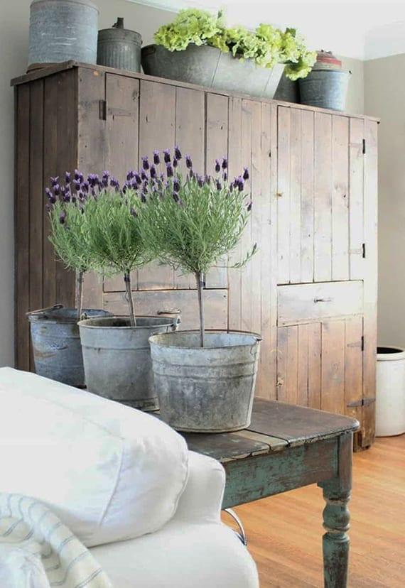 rustikales wohnzimmer interieur mit antikem kleiderschrank holz und pflanzengefäßen aus zink auf altem sideboard holz hinter dem sofa