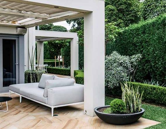 moderne gartengestaltung mit gartenterrasse und gemütlicher sitzecke ünter pergola und schwarzer outdoor-pflanzenkübel rund