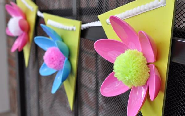 girlande für kinderpartys basteln aus holz, bunten plastiklöffeln und pompons
