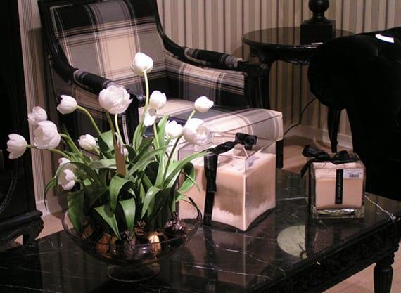 elegante tischdekoration mit weißen tulpen und weißen kerzen für ein schwarzes interieur mit couchtisch aus schwarzem marmor