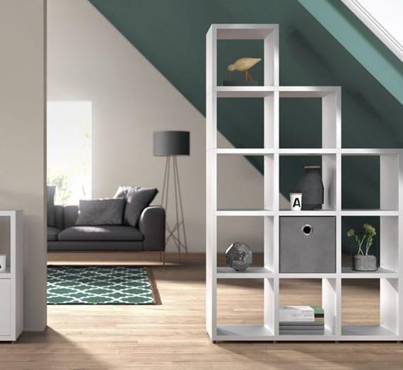 einzimmerwohnung unter dachsräge modern gestalten mit wandfarbe grün und praktisch einrichten mit sofa grau. stehlampe grau, teppich grün, parketboden und stufenregal weiß