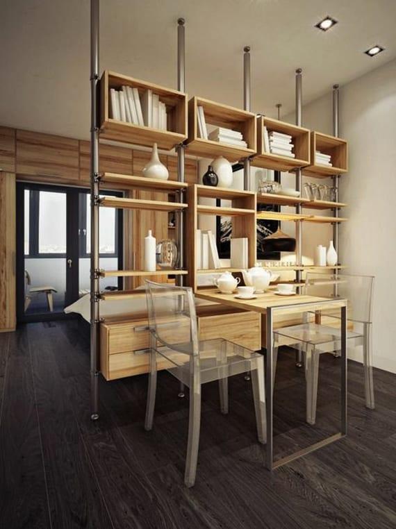 einrimmerwohung mit kleinem essbereich aus holztisch mit zwei stühlen aus acrylglas und bett hinter holzregalsystem