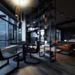 luxus studio apartment mit schwarzem interieur, dunklem holzboden, rundem esstisch mit metallstühlen schwarz,metallbücherregal schwarz als raumteiler, designer doppelbett