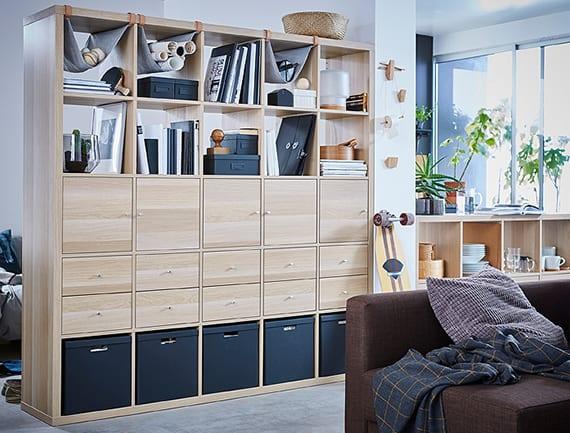 praktische raumteilung und gestaltung in einrimmerwohnungen mit holzregal, schwarzen aufbewahrungskisten, schubladen und türen