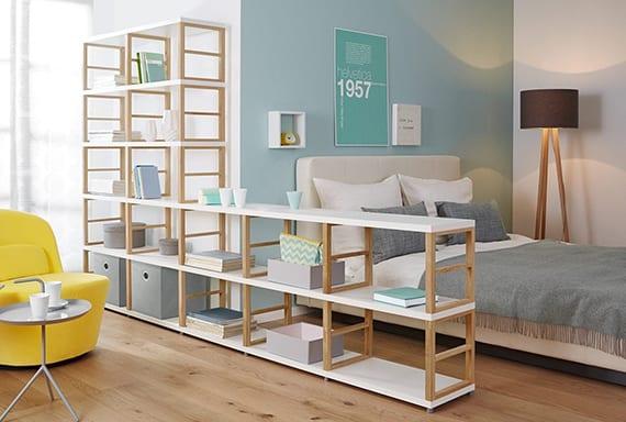 modernem regalsystem in holz und weiß für moderne raumteilung und raumgestaltung mit wandfarbe blau, doppelbett mit kopfteil weiß, holzbodenbelag und gelbem sessel mit rundem beistelltisch weiß