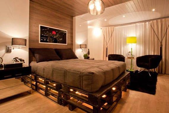 coole schlafzimmer Idee für moderne Einrichtung mit indirekt beleuchtetem DIY Palettenbett, Nachttschen in Spiegelglas, Akzentwand und Deckengestaltung mit Holz, Sitzecke mit schwarzem Teppich und zwei schwarzen Stühlen vor Fenster mit weißen Vorhängen