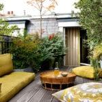 gemütliche terrassengestaltung kleiner dachterrasse mit gelben sitzkissen und rundem kafeetisch rattan auf holzdiele