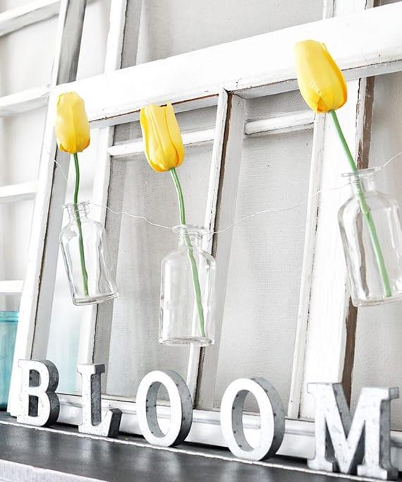 elegante wanddeko idee mit weißen holzfensterrahmen und gelben tulpen in kleinen glasflaschen-vasen