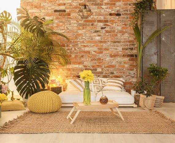 wohnzimmer gemütlich einrichten mit vielen grünen pflanzen, diy Palett-Sofa mit weißen Polstern und Dekokisen in gold vor Ziegelwand, Holztablett-Kaffeetisch und gelbem strick-puff auf Sesal-teppich