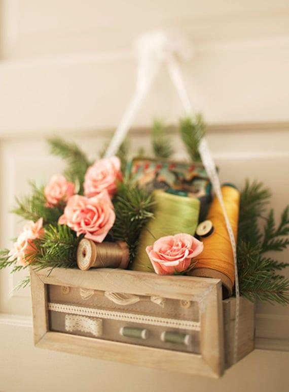 coole Türkranz alternative mit rosen, nadelbaumzweigen und bunten fadenspulen in kleiner holzkiste
