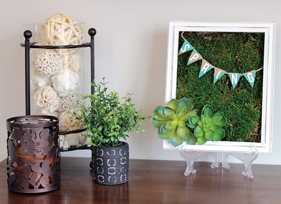 sideboard dekorieren mit Moos und dekorativen Bällen in Glasvase
