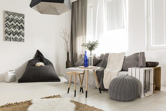 attraktive einrichtung kleiner wohnzimmer im skandi-stil mit weißem holzboden, diy beistelltisch aus holzkisten, zwei runden Holztischen, gestricktem Puff grau, Sitzsack Dunkelgrau, Sofadecken und Kissen in weiß und grau,sesal teppich und moderner Hängelampe schwarz