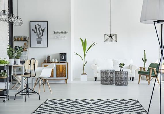 wohn-essbereich modern und belebend einrichten im schwarzweißen skandi-Stil mit modernen metallleuchten, skandinavischem teppich, runden metalltischen vor weißem sofa und holzesstisch mit zweifarbigen esstischstühlen