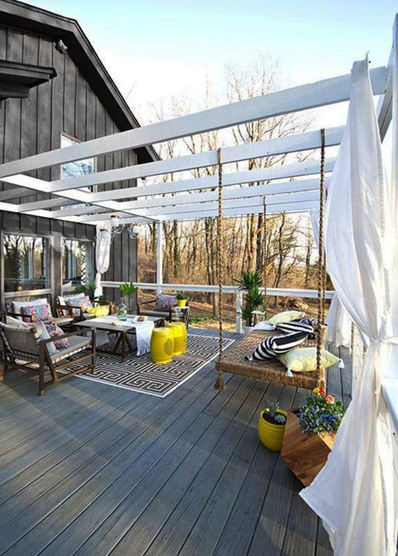 super coole terrassengestaltung in weiß und grau mit holzpergola, gardinen, hängebett, lounge-ecke mit teppich, marokkanischen hocker gelb und begrünung in holzkübel