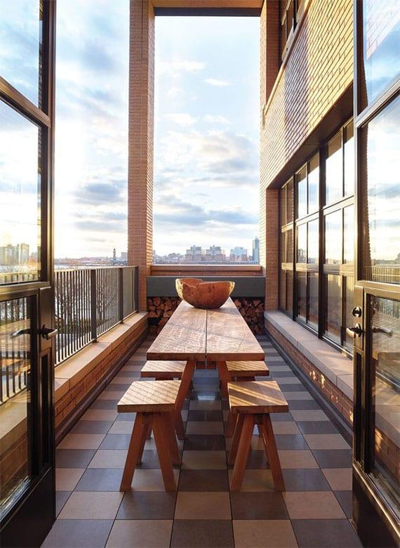 kleine rooftop terrasse als sommer-esszimmer einrichten mit holzesstisch und sitzbänken aus massivholz, bodenflisen in beige und braun, verglasung mit fenstersprossen und metallstabgeländer