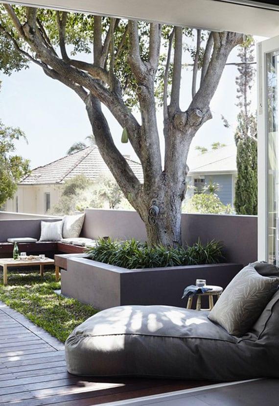 schicke terrassengestaltung mit bodenbegrünung, baum in hochbeet, eckbank, liegesack grau