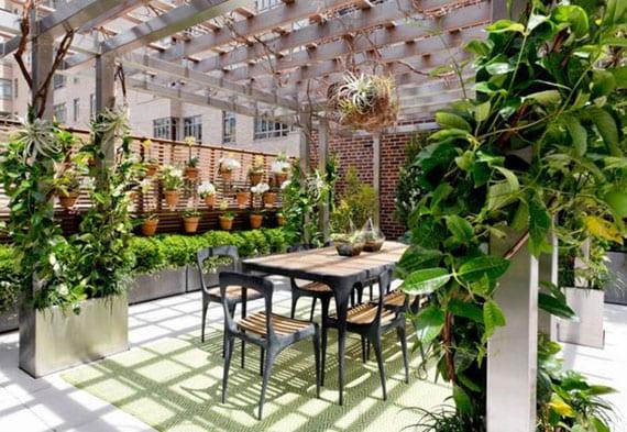 gemütliche terrassengestaltung und begrünung mit Kletterpflanzen und Buchsbäume in rechteckigen Metall-Hochbeeten, vertikalem Topforchideen-Garten, esstisch für acht personen aus holz und Zink, teppich grün