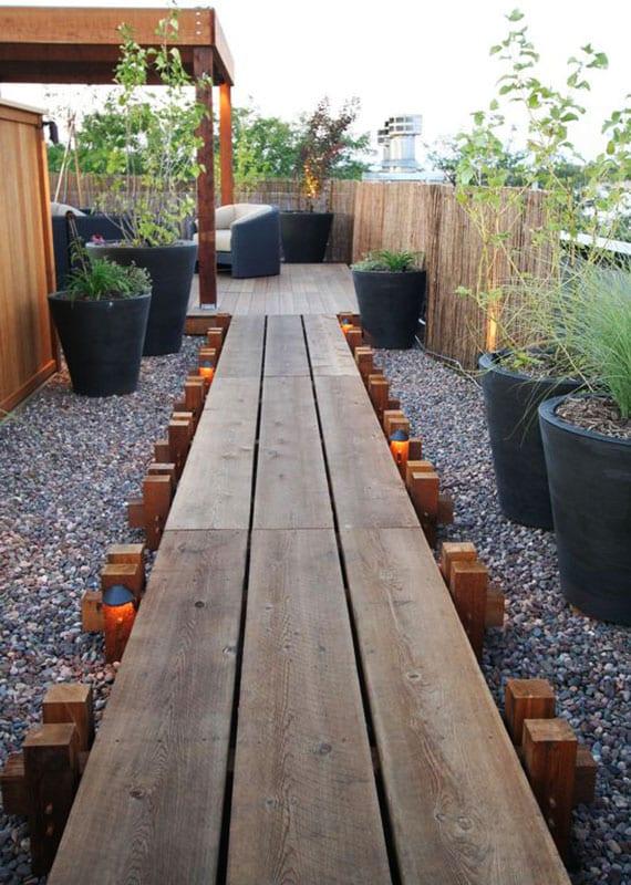 kreative gestaltungsidee für dachterrassen mit kiesbodenbelag und holzsteg zum lounge-bereich mit holzpergola auf holzpodest, runde blumenkübel schwarz, sichtschutz mit bamboo zaun