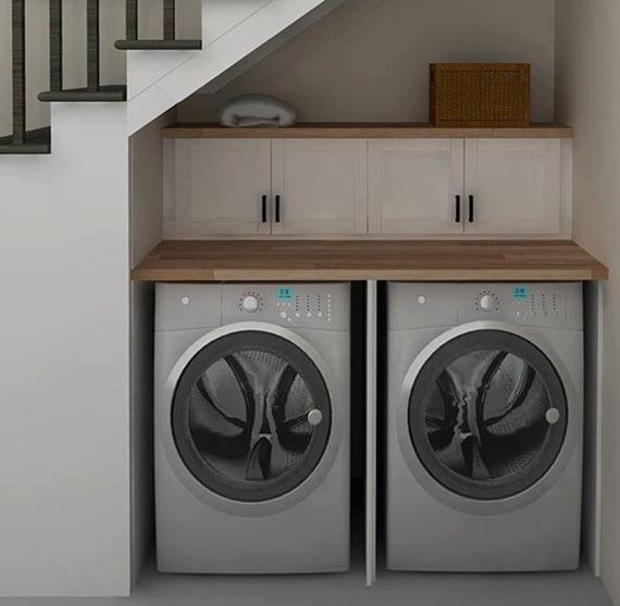 platzsparender waschraum mit waschmaschine, trockner und arbeitsplatte in treppennische einrichten