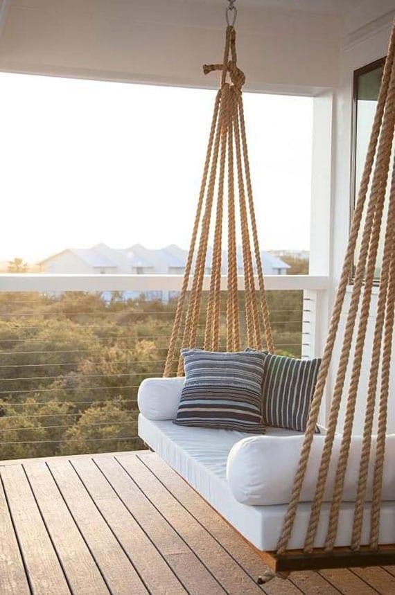coole terrassengestaltung überdachter terrasse mit holzdiele, stahlseilgeländer und selbstgebautem schaukelbett aus holz und seil mit weißen polsterkissen