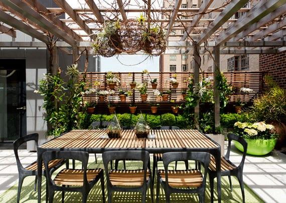 moderne gartenmöbel aus Teakholz und Zinkguss für rooftop terrasse mit vertikalem garten aus orchideen, pergola aus metall und reiben, hängende blumendeko mit luftpflanzen, buchsbäumen in metallkübeln und sichtschutz aus holzlatten
