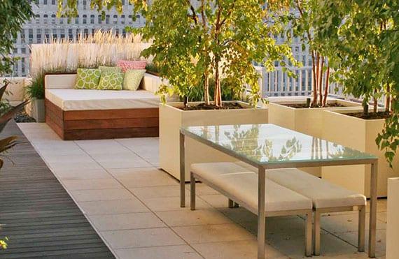 idee für moderne rooftop terrassengestaltung in beige und holz mit rechteckigen blumenkübeln weiß und ecksessel holz mit ecksichtschutz aus grasbegrünung
