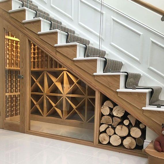 coole ideen für den treppenunterbau als kleiner weinkeller mit verschiedenen weinregalen aus holz  und als kaminholzregal unter moderner holzinnentreppe mit weißen stufen und glasgeländer