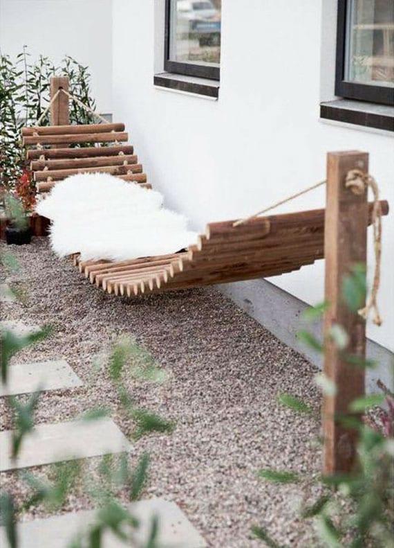 coole garten idee für gartengestaltung mit kiesboden, gartenweg aus rechteckigen trittsteinen und selbtgemachter hängematte aus rundholz mit weißem pelzteppich