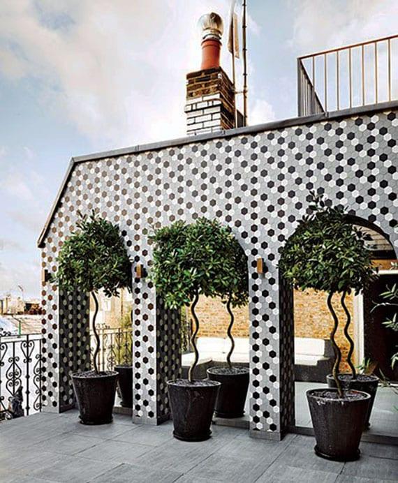 attraktife wandgestaltung einer dachterrasse mit mosaik, bogen-ganzkörperspiegeln und dekorativen bäumen in runden blumenkübeln schwarz