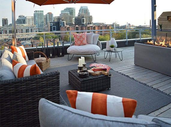 moderne dachterrasse mit glasgeländer einrichten mit rattanmöbeln, teppich grau, designer-lounge sessel mit rundem beistelltisch, großen metall-laternen, sonnenschirm orange und rechteckigem bio-kamin