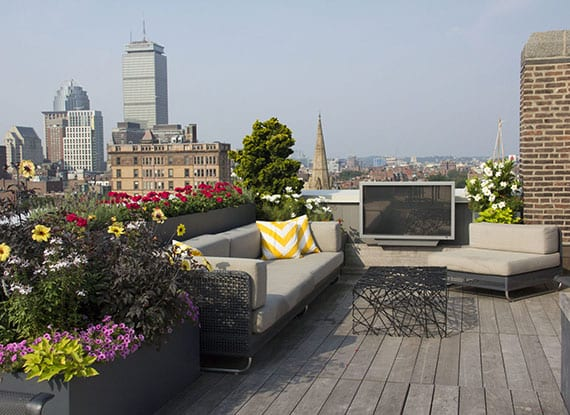 kleine rooftop terrasse modern einrichten mit Siitzecke und einem TV-Gerät