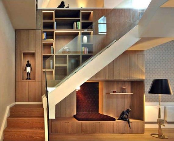 kreative wandgestaltung mit holzwandverkleidung, einbauregalen und sitzecke unter den stucffen einer metalltreppe mit glasgeländer