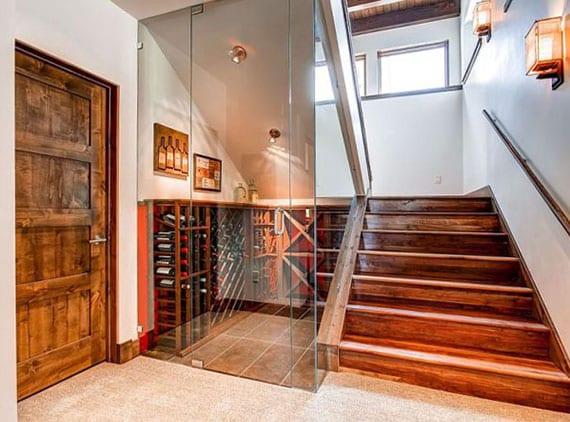 moderne und rustikale raumgestaltung flur mit antikem holztür, offener holztreppe und modernem weinraum unter treppe mit glastür und holzweinregalen