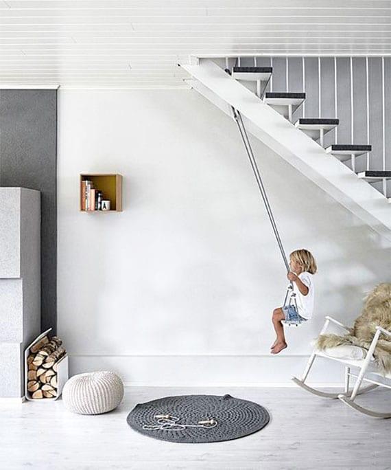 kreative ideen für kinderspielplatz zuhause mit einer schaukel unter offener innentreppe aus metall