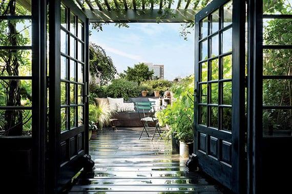 zugang zur dachterrasse durch schwarze holztüren mit sprossen_terrassengestaltung mit dunklem holzdiele, sitzbank mit dekokissen, holzpergola mit kletterpflanzen und üppiger begrünung