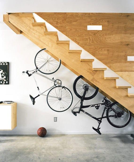 originelle raumgestaltung und aufbewahrungsidee für fahrräder unter offener holztreppe im wohnzimmer