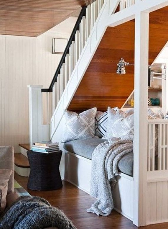 coole raumgestaltung mit kleinem Sofa unter holztreppe als raumteiler und kuscheliger sitzplatz im wohnzimmer