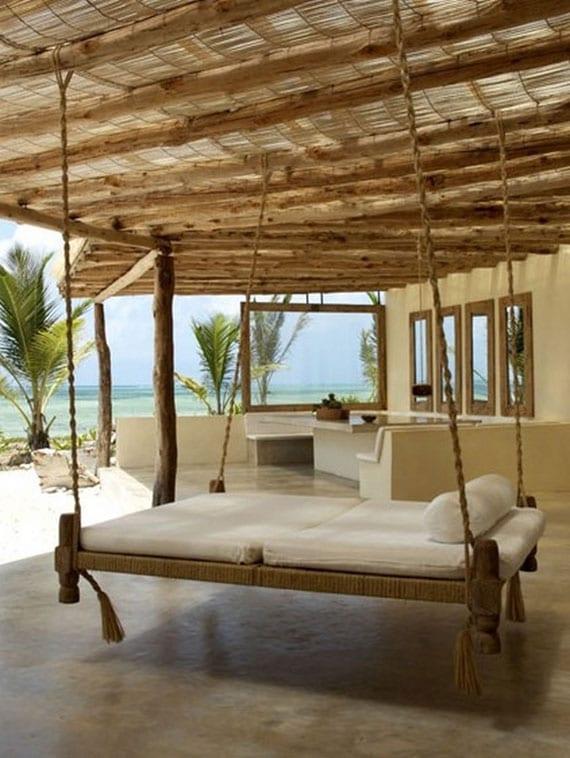 attraktive sommerhaus-veranda mit poliertem betonboden, überdachung aus rundholz und ried, diy hängebett holz und essbereich mit ausgemauerten sitzbänken