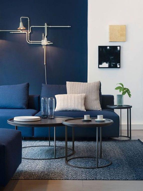 farbgestaltung idee für modernes wohnzimmer mit akzentwand und sofa in dunkelblau, runden couchtischen aus metall, teppich blau und coole wanddeko mit moderner wandleuchte weiß
