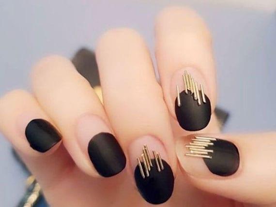 moderne maniküre mit schwarzem nagellack matt und goldenen nageleinleger