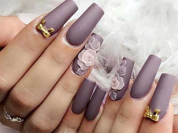 tolle manuküre für lange nägel mit hellrosa blumen und goldenen schleife-einlegern auf dunklen nagellack