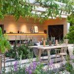 grünes wohnzimmer im garten mit holzesstisch und holzstühlen bunt, wohnwand mit kamin unter holzpergola