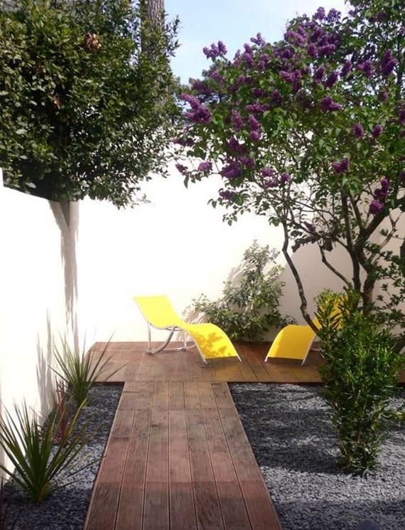 moderne gartengestaltung und coole gartenideen mit sitzbereich und wegführung aus holz, steingarten mit pflanzen und sträuchern im kies, gartenmauer weiß