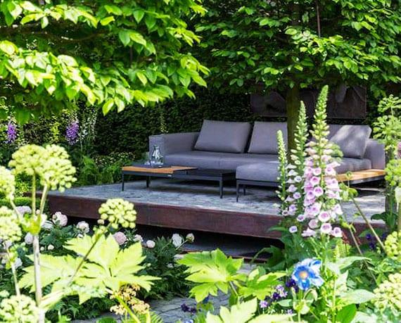 kreative lösungen für attraktive und moderne gartengestaltung mit ecksofa grau und metallcouchtisch schwarz auf schwebendem podest mit mosaikbodenbelag
